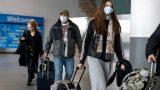 مسافرون يضعون كمامات للوقاية من فيروس كورونا في مطار جون اف كنيدي في نيويورك يوم 20 مارس اذار 2020. تصوير: بريندان مكدرميد - رويترز.